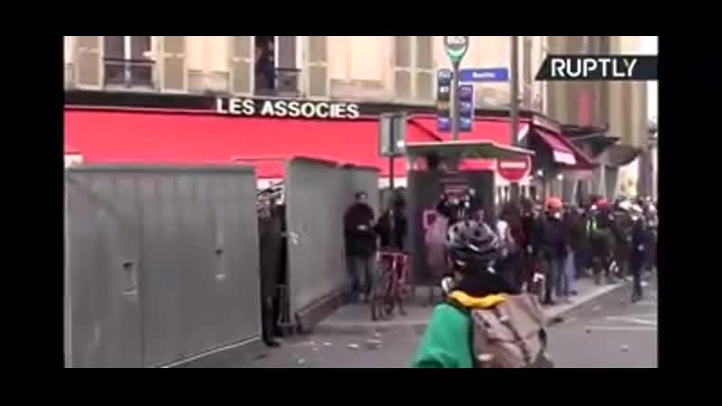 In Paris wirft die Polizei,versteckt hinter Paneelen,Granaten unter Missachtung jeglicher Sicherheitsregeln die Menschenmenge