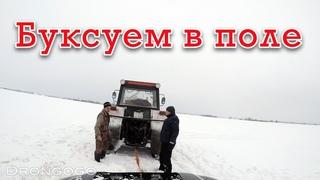Буксуем в поле с родней. Хорошо что трактор приехал на помощь. Засадил крузак в снегу.